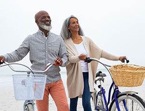 smiling older couple with bicycles